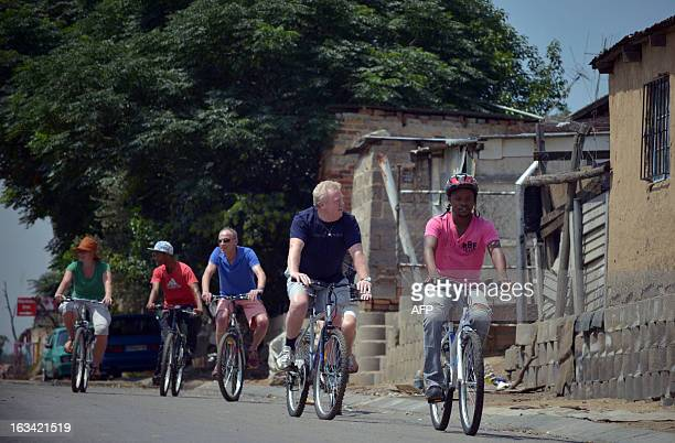 Tourists ride bicycles in Alexandra township Johannesburg on February 12 2013 Muludzi Tours offers the opportunity to discover one of the oldest and...