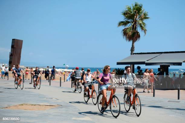 Tourists ride bicycles on a pedestrian street next to a beach of Barcelona on August 21 2017 four days after the Barcelona and Cambrils attacks that...