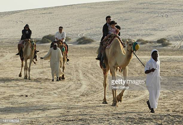 Tourists ride camels in the desert on October 30 2011 near Umm Sa'id Qatar Camel safaris and fourwheel drive tours of the desert are popular...