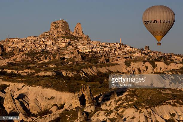 Tourists ride hot air balloon near the town of Uchisar on April 17 2016 in Nevsehir Turkey Cappadocia a historical region in Central Anatolia dating...