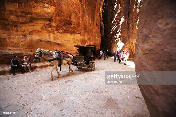 Tourists ride in a carriage pulled by a horse as they visit the legendary Petra Jordan's most famous tourist attraction on April 3 2015 in Petra...