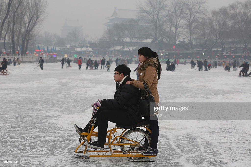 Tourists ride on specially constructed 'ice-bicycle' on the frozen Houhai Lake during severe pollution on February 3, 2013 in Beijing, China. Houhai Lake is a popular place for winter sport and entertainment in Beijing.