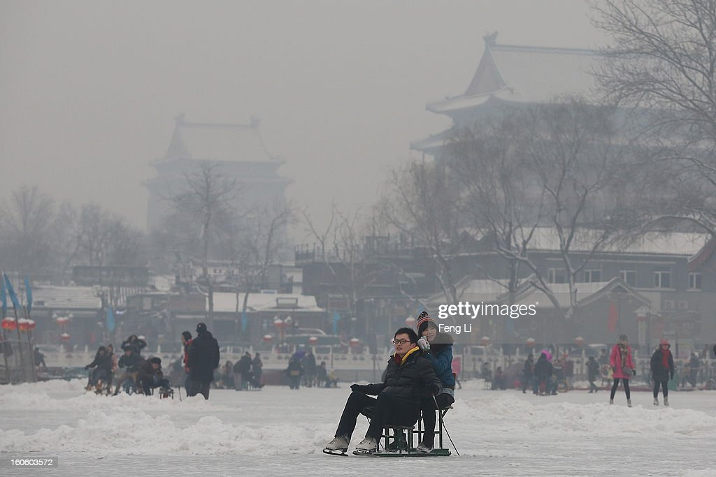 Tourists ride on specially constructed 'ice-chairs' on the frozen Houhai Lake during severe pollution on February 3, 2013 in Beijing, China. Houhai Lake is a popular place for winter sport and entertainment in Beijing.