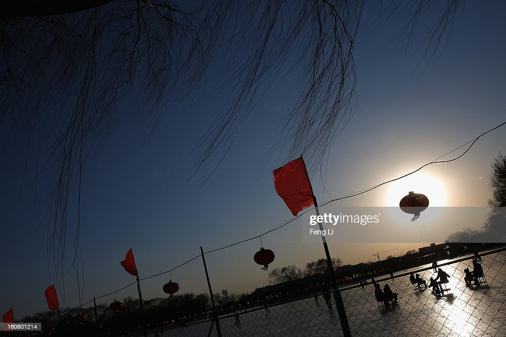 Tourists ride on specially constructed 'ice-chairs' on the frozen Houhai Lake during sunset on February 6, 2013 in Beijing, China.