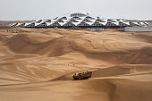 Tourists ride past the Desert Lotus Hotel under construction in Xiangshawan Desert also called Sounding Sand Desert on July 17 2013 in Ordos of Inner...