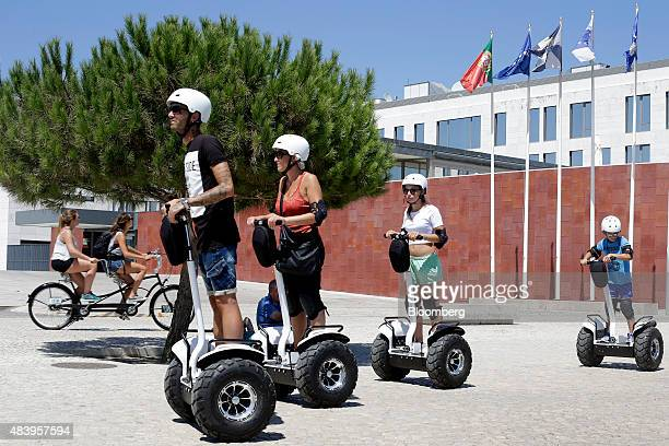 Tourists ride Segway electric vehicles along the Tagus river waterside in Lisbon Portgual on Saturday July 25 2015 Lisbon is joining other European...