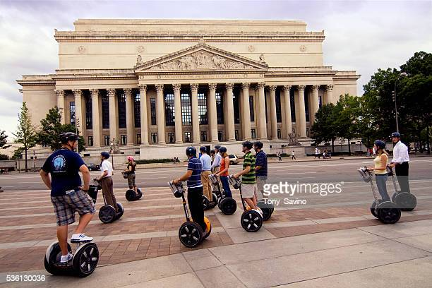 Tourists ride segways in front of the Archives of the United States building