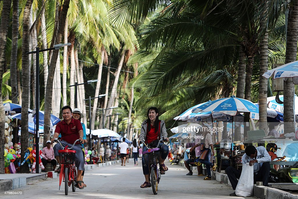 Tourists ride tandem bicycles past market stalls along a pathway next to Bang Saen beach near Pattaya Chonburi province Thailand on Thursday May 29...