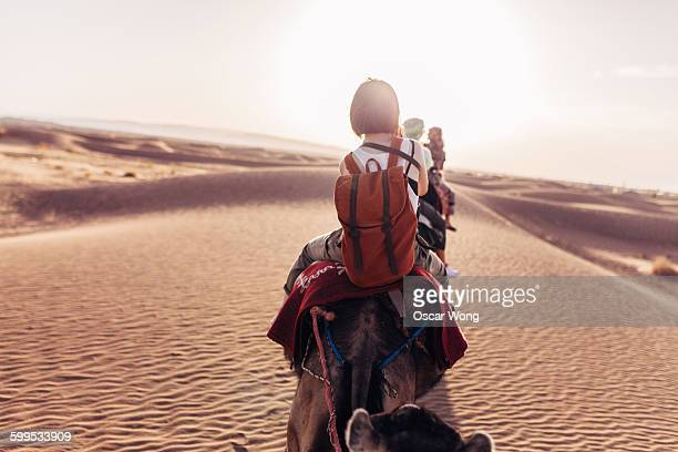 Tourists riding on camels in the Sahara desert