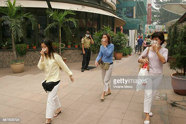 Tourists seek protection from the deadly haze by covering their nose and mouth while walking along Bukit Bintang Kuala Lumpur's elegant shopping area...