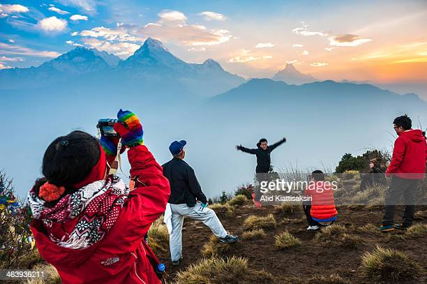 Tourists sightseeing at Pool Hill during sunrise over the Annapurna mountain range