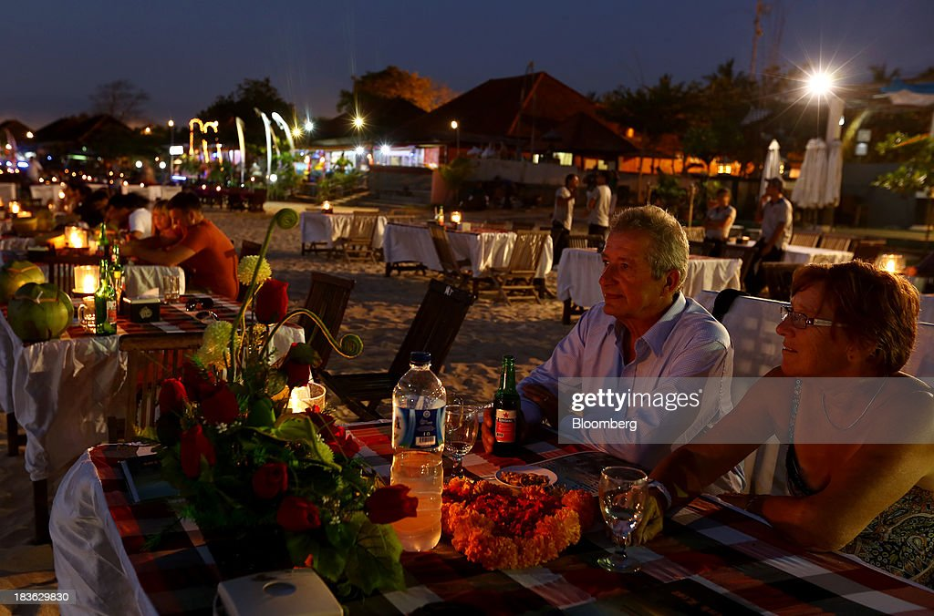Tourists sit at a beachside restaurant in the evening in Jimbaran, Bali, Indonesia, on Saturday, Oct. 5, 2013. Indonesia's central bank kept its key interest rate unchanged after its most aggressive tightening cycle in almost eight years as inflation pressure eased. Photographer: SeongJoon Cho/Bloomberg via Getty Images
