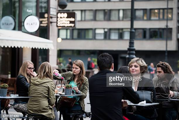 Tourists sit at outdoor cafe tables near St Stephen's basilica in central Budapest Hungary on Friday May 15 2015 Housing in Hungary is on the mend...
