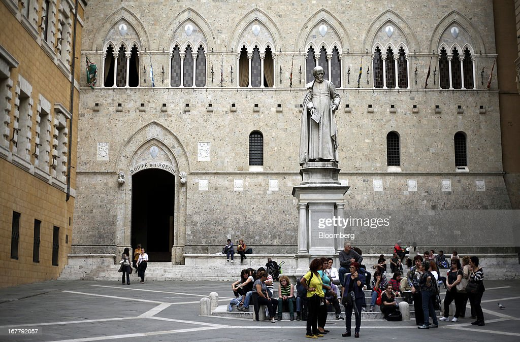 Tourists sit beneath a statue of Sallustio Bandini in Piazza Salimbeni, near the headquarters of Banca Monte dei Paschi di Siena SpA in Siena, Italy, on Monday, April 29, 2013. An Italian judge rejected a request by prosecutors to seize as much as 1.95 billion euros ($2.5 billion) of assets held by Nomura Holdings Inc. as they probed how Banca Monte dei Paschi di Siena SpA used derivatives to conceal losses. Photographer: Alessia Pierdomenico/Bloomberg via Getty Images