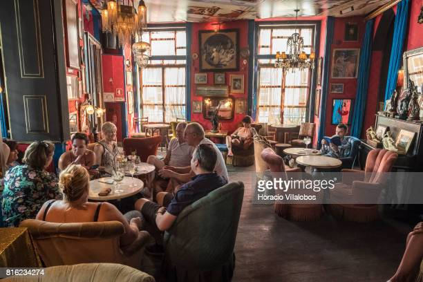 Tourists sit in a room reproducing typical brothel decoration at 'Pensao Amor' on July 14 2017 in Lisbon Portugal 'Pensao Amor' used to be a five...