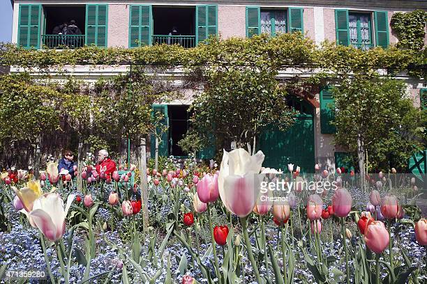Tourists sit in front of the house of Claude Monet on Monday 27 2015 in Giverny France The famous French impressionist painter Claude Monet lived in...