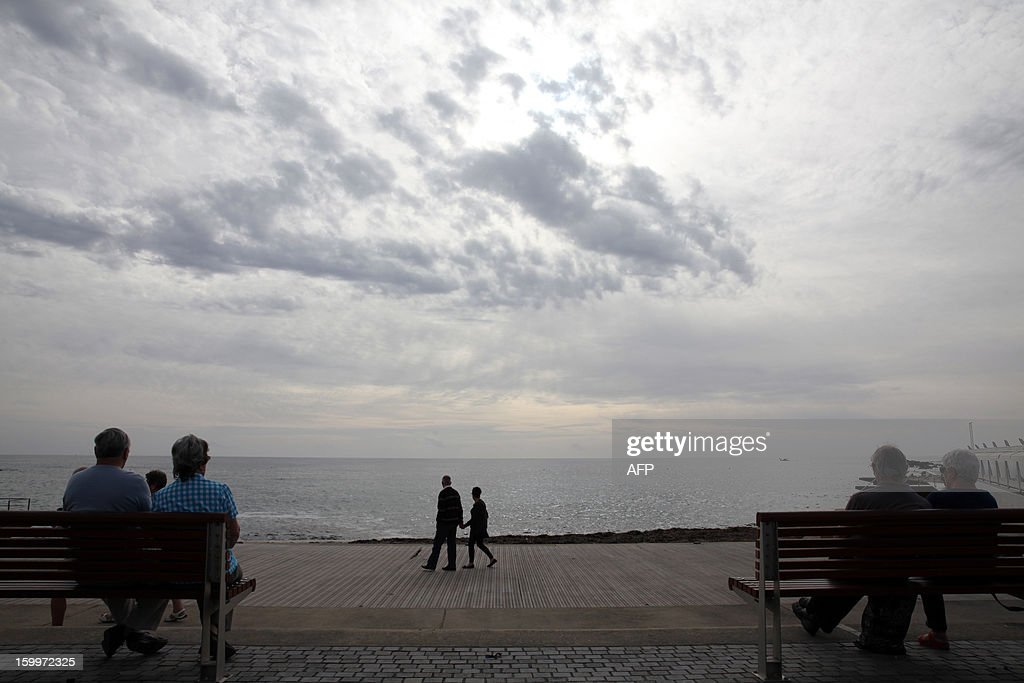 Tourists sit looking out at the sea in the Cypriot coastal city of Paphos on January 24, 2013. Tourist arrivals to the Mediterranean island for January-December 2012 increased 3.0 percent reaching 2.46 million visitors, up from 2.39 million in 2011. AFP PHOTO / YIANNIS KOURTOGLOU