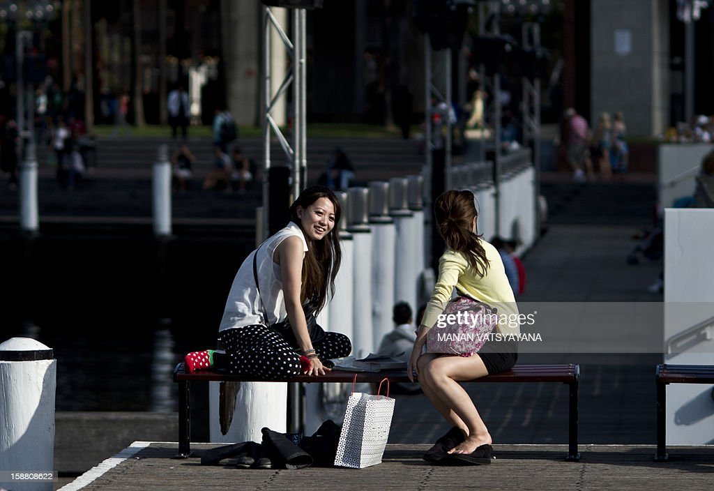 Tourists sit on a bench in Sydney's Darling Harbour area on December 30, 2012. International visitors to Australia are expected to increase from over 5.9 million in 2010-11 to nearly 8.2 million in 2020-21, an average annual growth rate of three percent, reported Tourism Research Australia (TRA).