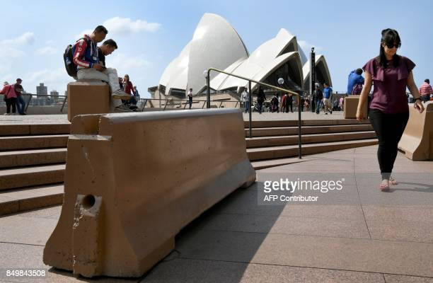 Tourists sit on a bollard newly installed to help protect tourists and locals from a terror attack at the Sydney Opera House on September 20 2017 A...