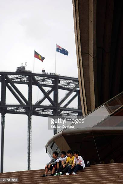 Tourists sit on the steps of the Sydney Opera House as he Aboriginal and Australian flags fly on the Sydney Harbour Bridge on the day Australian...