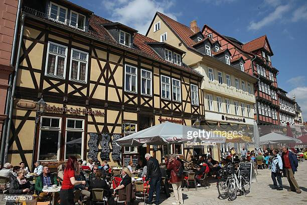 Tourists sit outside on the main square among halftimbered houses on April 20 2014 in Quedlinburg Germany Quedlinburg located in the Harz region...