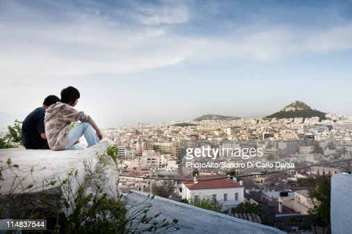 Tourists sitting on rock overlooking Athens, Greece and Mount Lycabettus