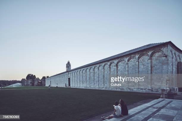 Tourists sitting outside Camposanto monumentale, Pisa, Tuscany, Italy