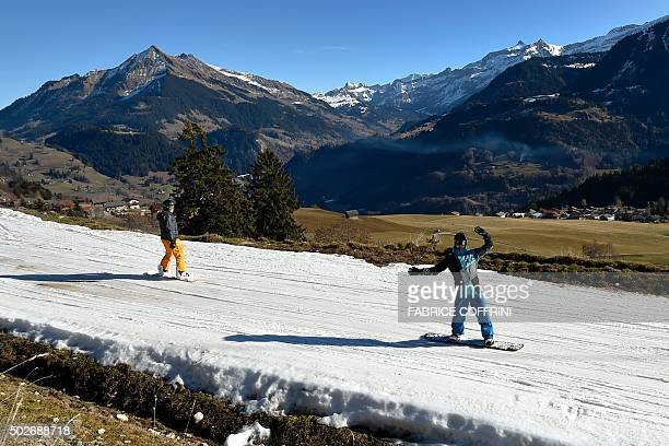Tourists ski on a thin layer of snow back to the resort of Leysin Swiss Alps on December 28 2015 In a season traditionally associated with iceskating...