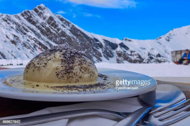 Tourists skiers enjoy the local food speciality Germknoedel made of yeast dough and a mountain view the sun at the Tuxer Joch Haus mountain hut on...