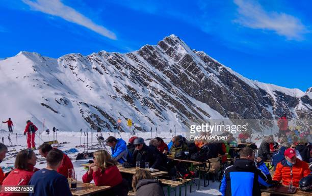 Tourists skiers enjoy the mountain view the sun at the Tuxer Joch Haus mountain hut on the glacier of Hintertux on March 12 2017 in Hintertux Austria