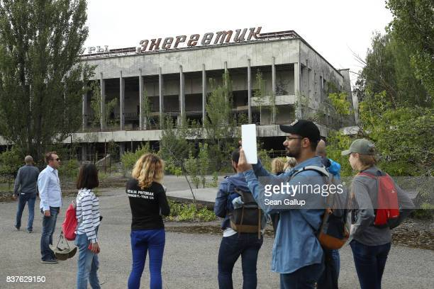 Tourists snap photos outside the former Energetika cultural center in the ghost town of Pripyat not far from the Chernobyl nuclear power plant on...