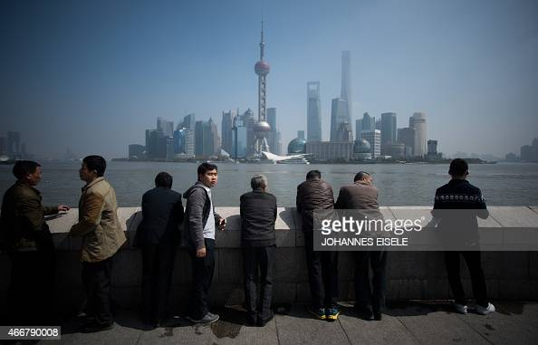 Tourists stand at the Bund in front of the financial district of Pudong in Shanghai on a sunny day on March 19 2015 AFP PHOTO / JOHANNES EISELE