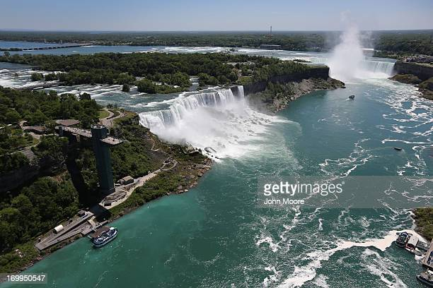 Tourists stand atop an observation tower on the American side overlooking the Niagara Falls on June 4 2013 at Niagara Falls New York The falls which...