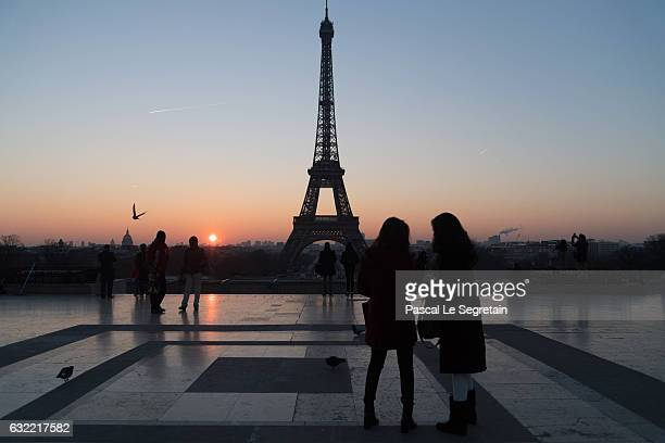 Tourists stand in front of the Eiffel tower at sunrise on January 18 2017 in Paris France
