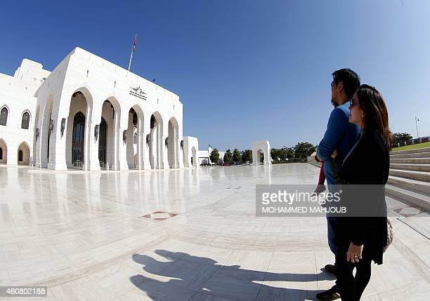 NEREIM Tourists stand in front of the Royal Opera on December 23 2014 in the Omani capital Muscat From desert camping to luxury hotels turtlewatching...