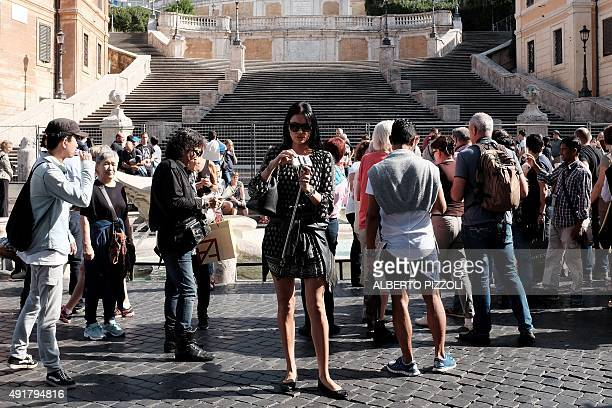 Tourists stand in front of the Spanish Steps closed to the public for restoration on October 8 2015 in Rome Work began on October 7 2015 to restore...