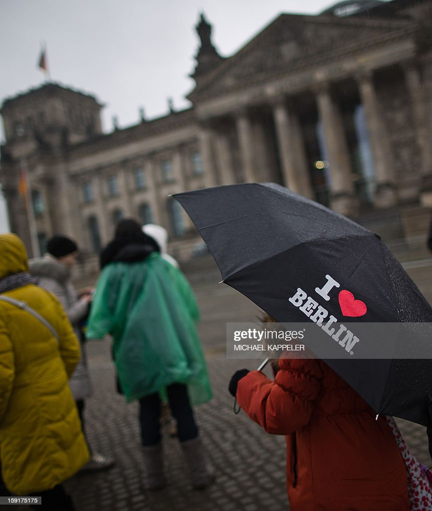 Tourists stand in the rain in front of the Reichstag building in Berlin, on January 9, 2013. Meteorologists forecast rainy weather for northern and eastern parts of Germany for the coming days.