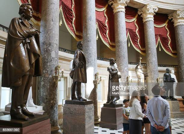 Tourists stand near a bronze statue of Confederate president Jefferson Davis that stands inside of Statuary Hall at the US Capitol August 17 2017 in...