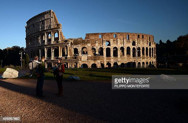 Tourists stand near the Colosseum at sunset on November 21 2014 in Rome AFP PHOTO / FILIPPO MONTEFORTE