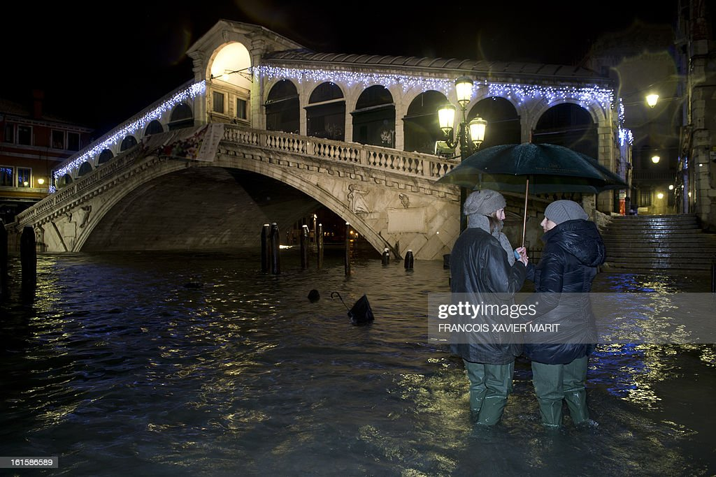 Tourists stand on a flooded quay in front of the Rialto bridge during an acqua-alta (high-water) late on February 11, 2013 in Venice. The 'acqua alta', a convergence of high tides and a strong sirocco, reached 143 centimetres around midnight.