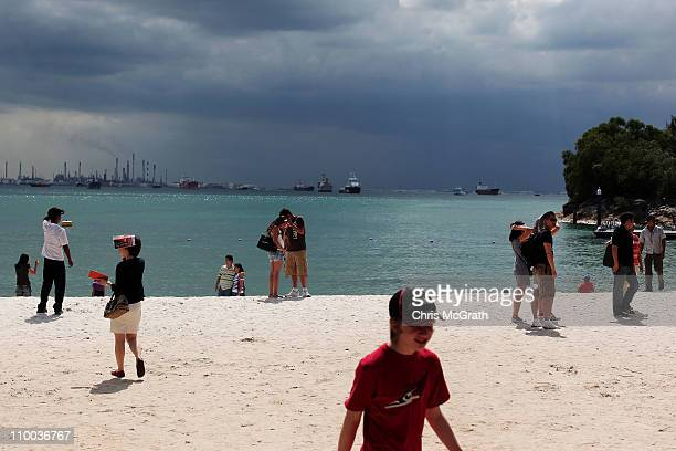 Tourists stand on the beach at Sentosa Island on March 13 2011 in Singapore Asia is currently experiencing a tourisim boom with 2010 reports showing...