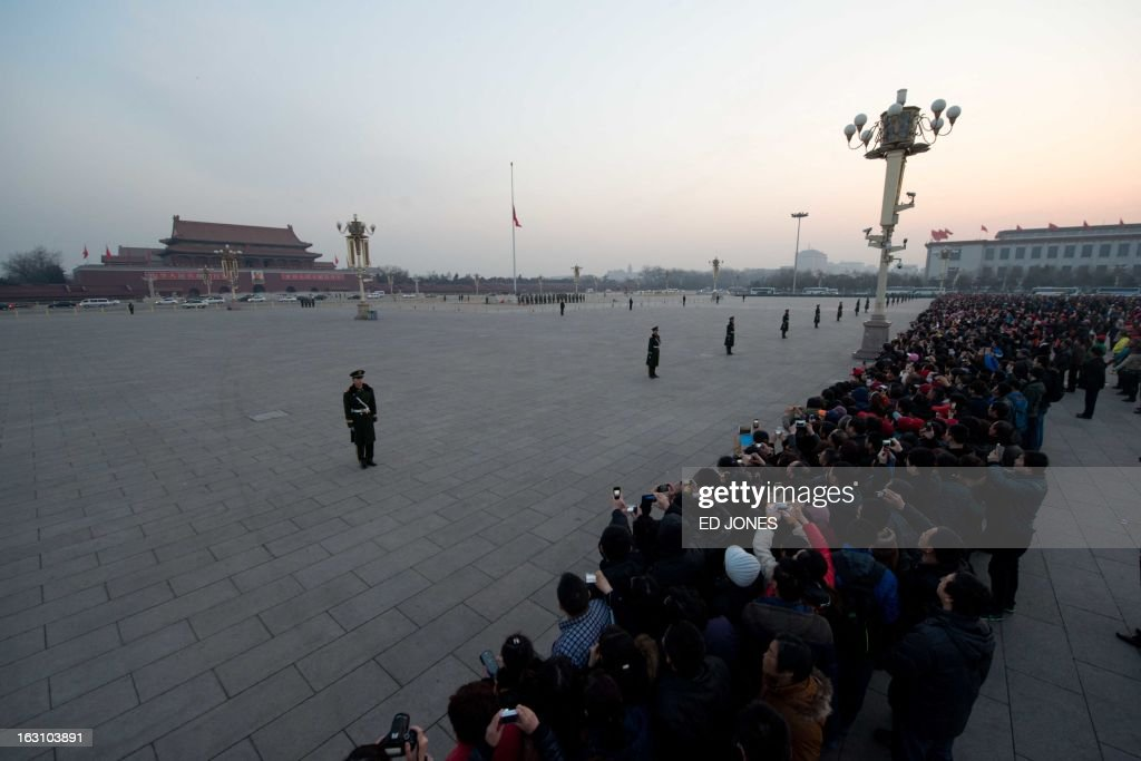 Tourists stand on Tiananmen Square to watch the daily flag-raising ceremony in Beijing early on March 5, 2013. Thousands of delegates from across China meet this week to seal a power transfer to new leaders whose first months running the Communist Party have pumped up expectations with a deluge of propaganda. AFP PHOTO / Ed Jones