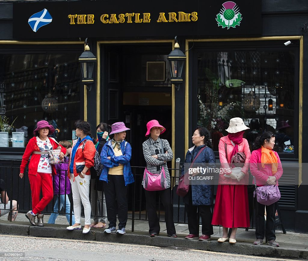 Tourists stand outside a pub in Edinburgh, Scotland on June 25, 2016, following the pro-Brexit result of the UK's EU referendum vote. The result of Britain's June 23 referendum vote to leave the European Union (EU) has pitted parents against children, cities against rural areas, north against south and university graduates against those with fewer qualifications. London, Scotland and Northern Ireland voted to remain in the EU but Wales and large swathes of England, particularly former industrial hubs in the north with many disaffected workers, backed a Brexit. / AFP / OLI