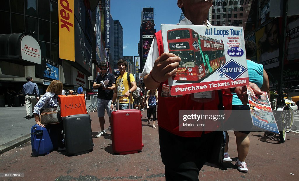 Tourists stand with their luggage as a tour bus hawker walks past outside the Marriott Marquis in Times Square on June 21, 2010 in New York City. Accused Times Square bomber Faisal Shahzad is slated to be arraigned this afternoon on ten counts of terror and weapons charges.