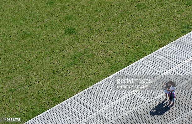 Tourists standing on a pedestrian platform read a map at the site where used to stay the former palace of republic and the Royal Palace in Berlin on...