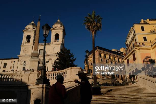 Tourists stands on the Spanish Steps with the church of Trinita dei Monti on the top on August 14 2017 at sunset in Rome / AFP PHOTO / Alberto PIZZOLI