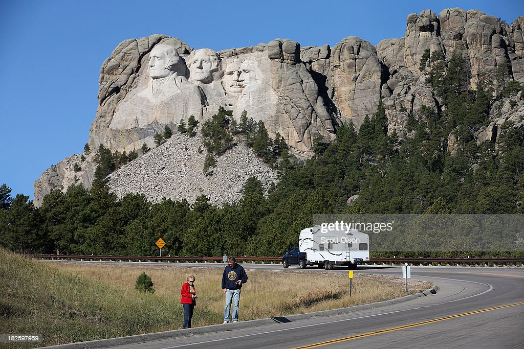 Tourists stop along the highway because the park is closed to view Mount Rushmore National Memorial on October 1, 2013 in Keystone, South Dakota. Mount Rushmore and all other national parks were closed today after congress failed to pass a temporary funding bill, forcing about 800,000 federal workers off the job. A bulletin issued by the Department of Interior states, 'Effective immediately upon a lapse in appropriations, the National Park Service will take all necessary steps to close and secure national park facilities and grounds in order to suspend all activities ...Day use visitors will be instructed to leave the park immediately...'