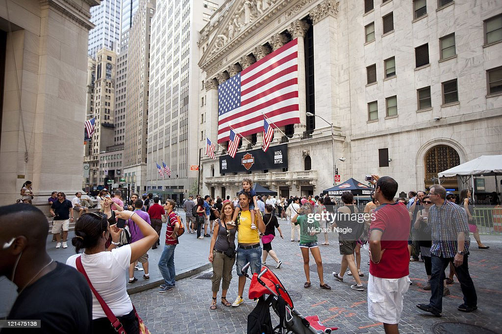 Tourists stop to take pictures in front of the New York Stock Exchange on August 19, 2011 in New York City. The Dow ends another volatile week, closing more than 100 points Down for the day.