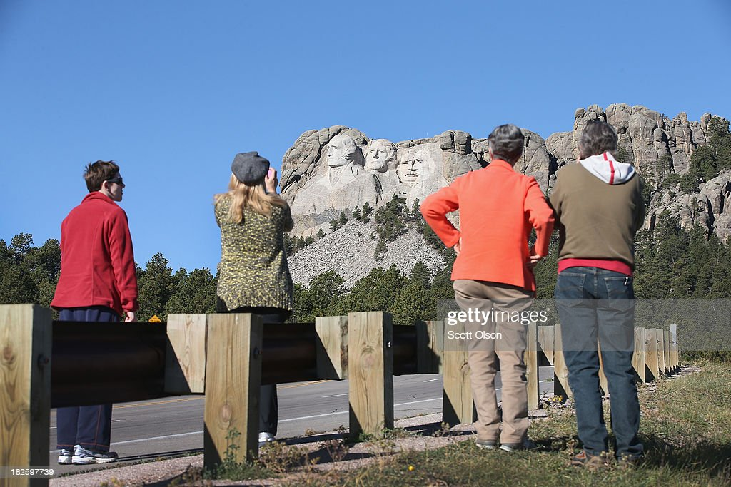 Tourists stop to take pictures near the entrance to Mount Rushmore National Memorial on October 1, 2013 in Keystone, South Dakota. Mount Rushmore and all other national parks were closed today after congress failed to pass a temporary funding bill, forcing about 800,000 federal workers off the job. A bulletin issued by the Department of Interior states, 'Effective immediately upon a lapse in appropriations, the National Park Service will take all necessary steps to close and secure national park facilities and grounds in order to suspend all activities ...Day use visitors will be instructed to leave the park immediately...'