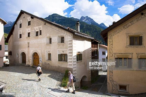 Tourists stroll in the Engadine Valley in village of Ardez with painted stone 17th Century restored houses Switzerland